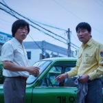 A destra uno sbalordito Kang-ho Song in un momento di A Taxi Driver di Hoon Jang (Taeksi Woonjunsa, Corea del Sud, 2017)