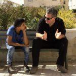 Il regista Amos Gitai a colloquio con un bambino durante West of the Jordan River di Amos Gitai (Israele, 2017)