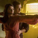 Romantiche lezioni di tiro con l'arco per Eve Hewson, grazie a Taron Egerton, durante Robin Hood - L'origine della leggenda di Otto Bathurst (USA, 2018)